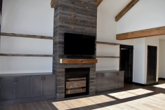 Reclaimed snowfence accent and timber mantel